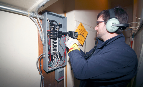 electrician inspecting electrical panel