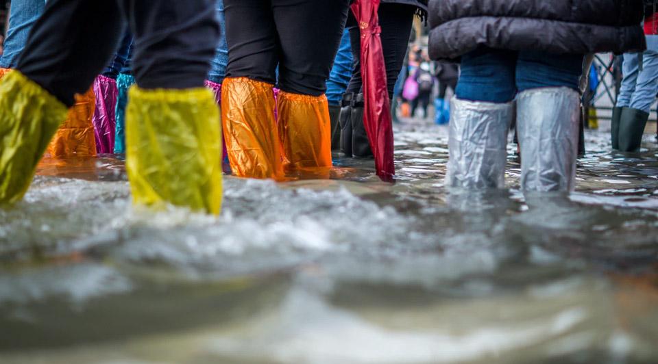 people walking in flood waters